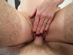 Slutty blonde milf is sitting on the bed with her stepson and seducing him